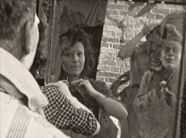 Séance de maquillage dans les décombres, photogramme extrait du film : « Puys » de Robert Absire, 8mm, 1945 ©Pôle Image Haute-Normandie